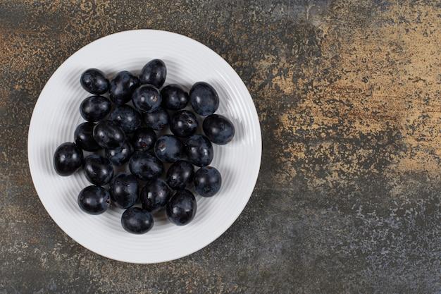 Fresh black grapes on white plate.