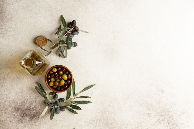 Fresh black and green olives and olive oil on concrete table. top view