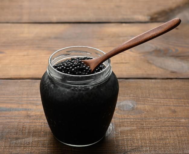 Свежая черная икра веслоноса в деревянной коричневой ложке и полная банка икры на деревянном столе, деликатес