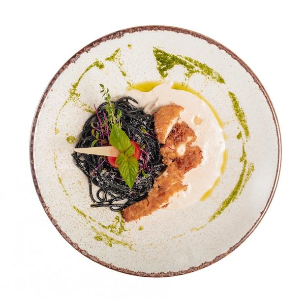 Fresh black tagliolini pasta with chicken in herbs