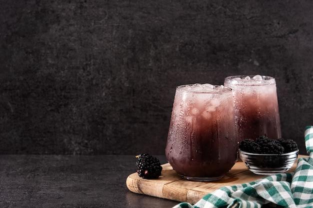 Коктейль из свежей ежевики в холодном стекле на черном камне