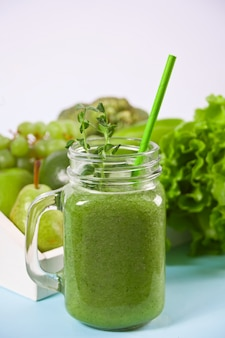 Fresh blended green smoothie in glass jar with fruit and vegetables . health and detox concept.