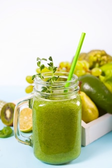 Fresh blended green smoothie in glass jar with fruit and vegetables. health and detox concept.