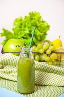 Fresh blended green smoothie in glass small bottle with fruit and vegetables . health and detox concept.