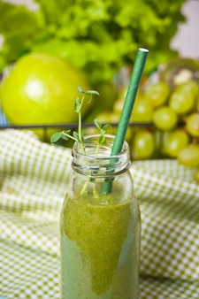 Fresh blended green smoothie in glass small bottle with fruit and vegetables. health and detox concept.