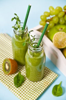 Fresh blended green smoothie in glass small bottles with fruit and vegetables . health and detox concept.