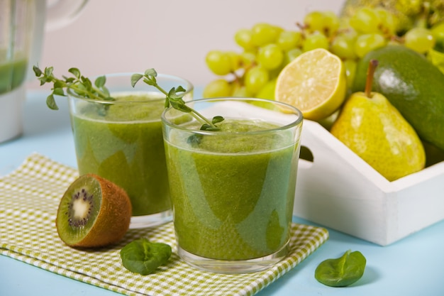 Fresh blended green smoothie in glasses with fruit and vegetables . health and detox concept.