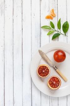 Fresh blood orange fruits on white plate with knife