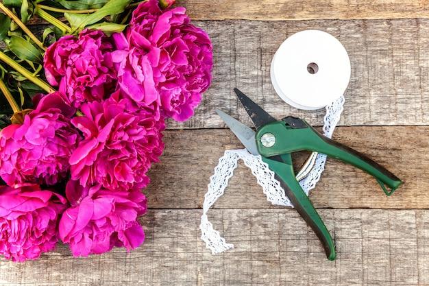 오래 된 허름한 소박한 나무 배경에 신선한 피 핑크 마젠타 모란 꽃 꽃다발과 정원 도구 가위 정리기