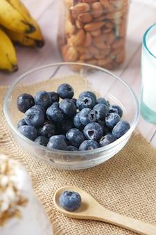 Свежие голубые ягоды в миске с банановым молоком и миндалем на столе