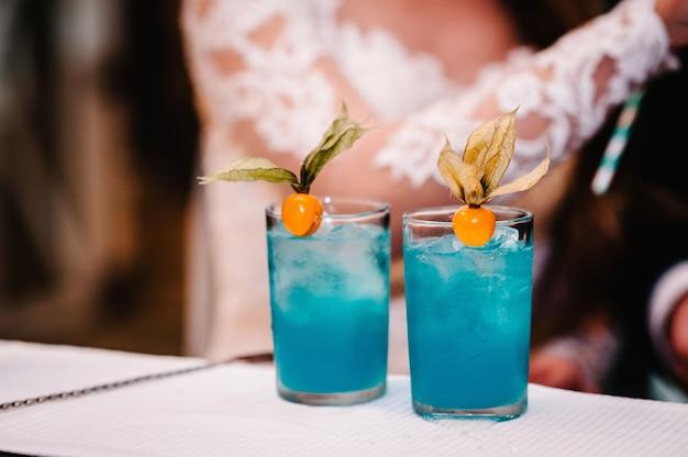Свежий синий сок в стакане на барной стойке на фоне жениха и невесты
