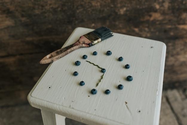 フレッシュブルーマットラウンドブルーベリー。木製の白い椅子に時計の形に折りたたまれたベリーが横たわっています