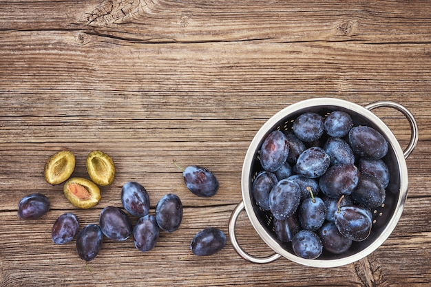 Fresh blue plums in rustic colander on old wooden table. organic food. top view, copyspace, toned
