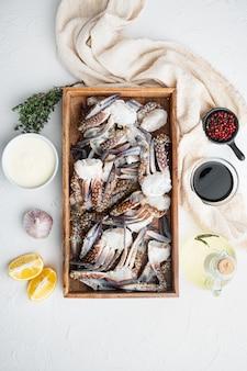 Свежее мясо синего плавательного краба, в деревянной коробке, на белом фоне, плоский вид сверху