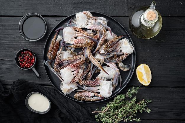 Свежее мясо синего плавательного краба, на тарелке, на фоне черного деревянного стола, плоский вид сверху