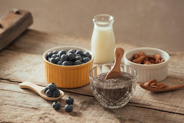 나무 판자에 우유를 넣은 신선한 블루베리, 아몬드, 치아 씨. 이상적인 건강한 아침 식사 개념입니다.