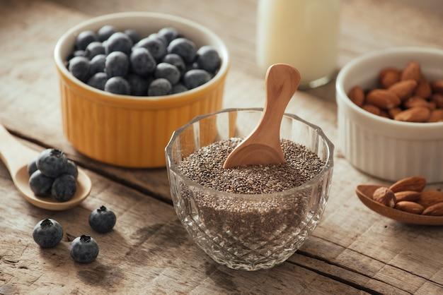 木の板にミルクと新鮮なブルーベリー、アーモンド、チアシード。理想的な健康的な朝食のコンセプト。