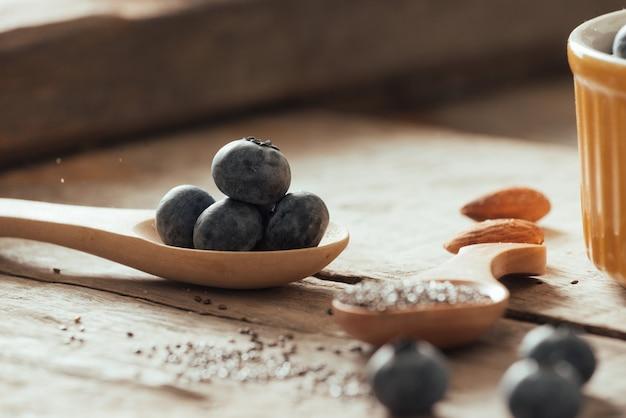 古い木製のテーブルに新鮮なブルーベリーとチアシード