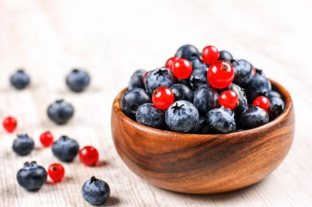Свежие ягоды черники и красной смородины с листьями мяты в деревянной миске на мешковину. диетическое питание, веганские ягоды
