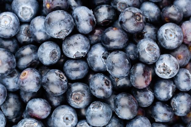 あなたのテキストのためのコピースペースと新鮮なブルーベリーの背景。ボーダーデザイン。ビーガンとベジタリアンの概念。ブルーベリーベリーのマクロテクスチャー。夏の健康食品。バナー。