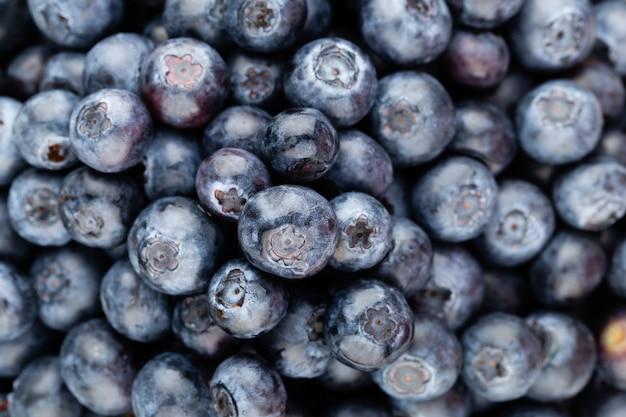 テキストのコピースペースと新鮮なブルーベリーの背景。ボーダーデザイン。ビーガンとベジタリアンのコンセプトです。ブルーベリーの果実のマクロテクスチャ。夏の健康食品。バナー。