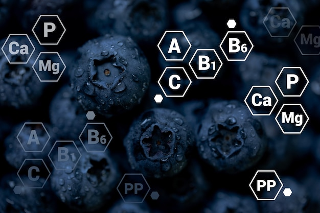 Fresh blueberries background with letter designations of vitamins and minerals healthy food vegan and vegetarian concept