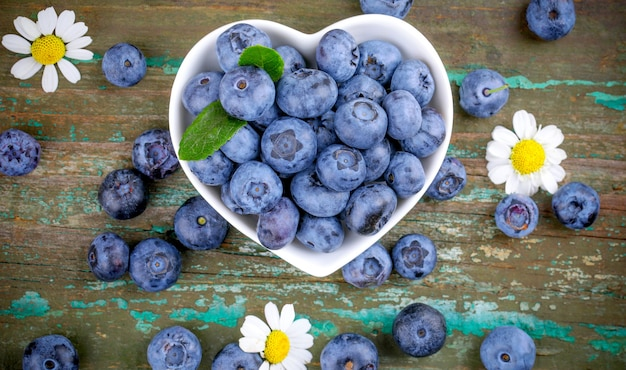 Fresh blueberries in a bowl in the shape of a white heart on an old wooden background close-up
