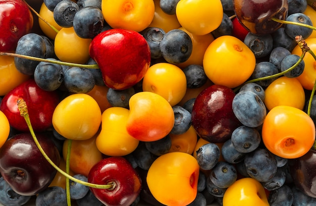 Fresh blueberries and cherries background, top view