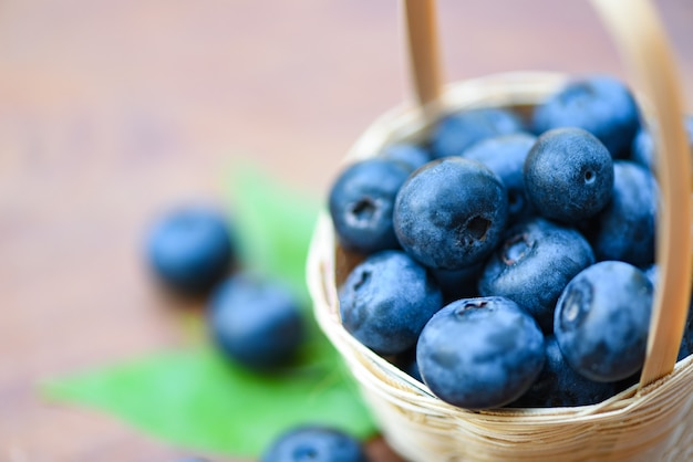 Fresh blueberries fruit in basket and green leaves on wooden background