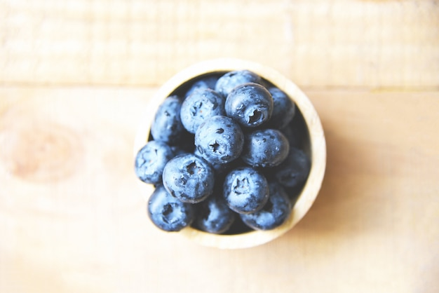 Fresh blueberries fruit in bowl on wooden table