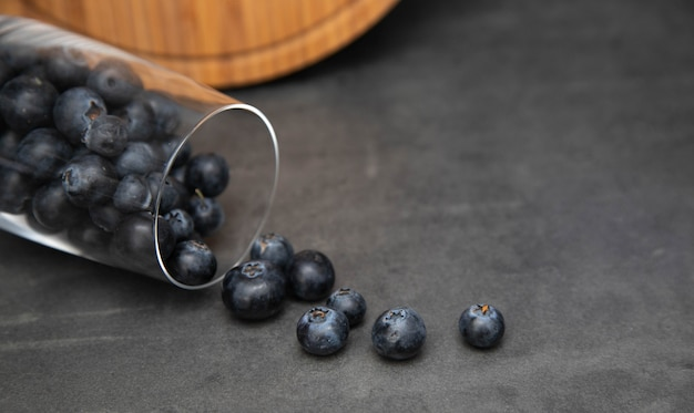 Fresh blueberries in a glass bowl. delicious blueberries scattered from a glass cup.