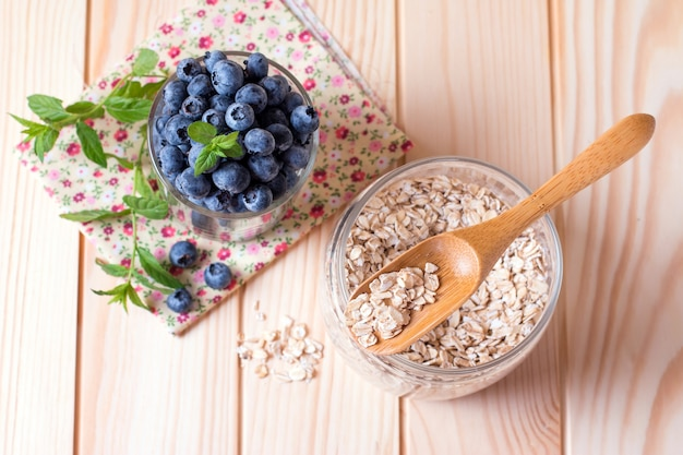Fresh blueberries in a glass of oat flakes