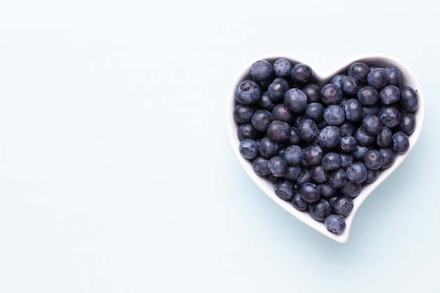Fresh blueberries, in a heart shaped bowl on a wooden background.