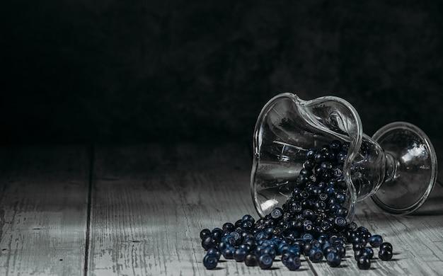 ガラスのボウルに新鮮なブルーベリー。軽い木製のテーブルの上にジューシーで新鮮なブルーベリー。暗い背景にブルーベリー。ブルーベリー抗酸化剤。健康食品と栄養の概念。