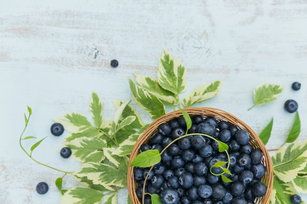 Свежая черника в корзине с видом сверху картины листьев. здоровая еда на белом столе макет