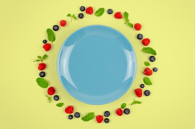Fresh blueberries, raspberries and mint leaf with blue plate.