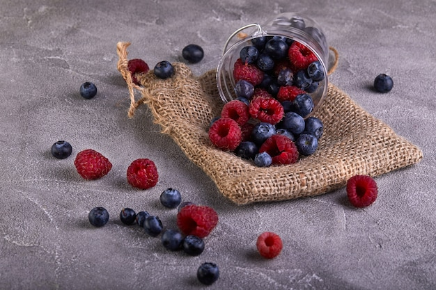 Fresh blueberries and raspberries scattered from a transparent bucket on a gray concrete