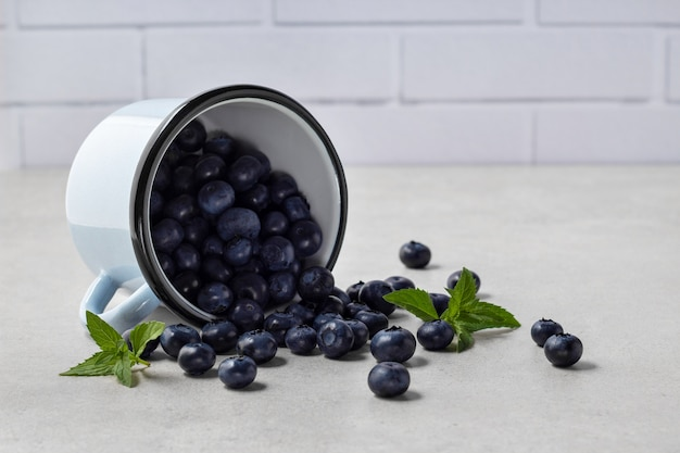 Fresh blueberries scattered from mug on grey table, space for text. ripe organic fruits