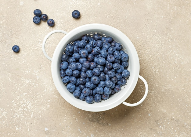 Fresh blueberries in a white metal sieve on beige color kitchen table, top view