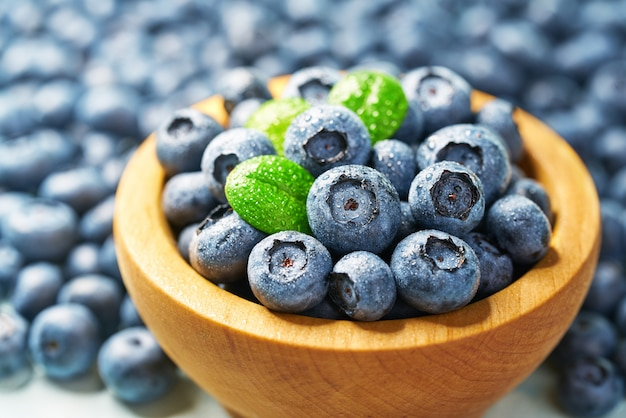 Fresh blueberries  with green leaves in a wooden bowl on a blueberries background, close-up