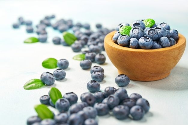 Fresh blueberries  with green leaves in a wooden bowl on a light background, with copy space.