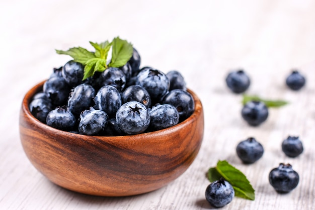 Fresh blueberries with green mint leaf in a wooden bowl on white table