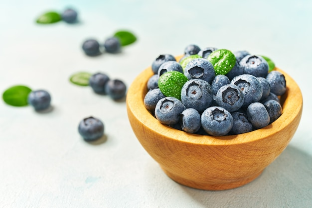 Fresh blueberries in a wooden bowl on a light background, with copy space. concept for healthy eating and nutrition.