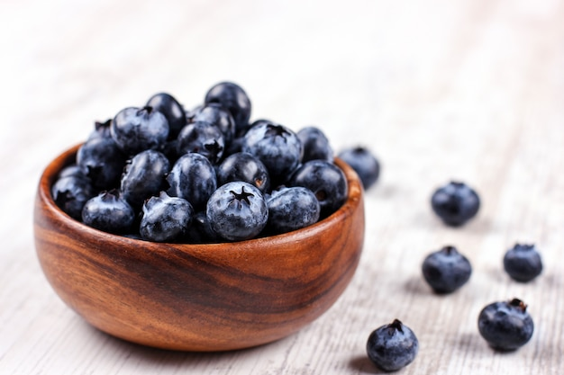 Fresh blueberries in a wooden bowl on white table