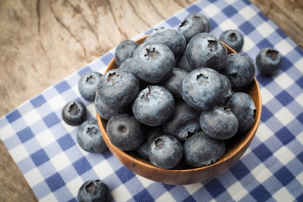 Fresh blueberries in wooden bowls on old wooden table background