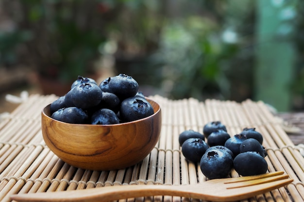 Fresh blueberries in wooden bowls on old wooden table with bokeh blurred background