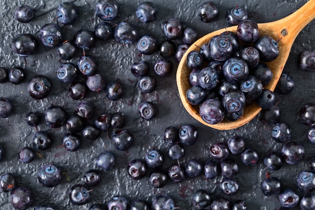 Fresh blueberries in a wooden spoon on stone table