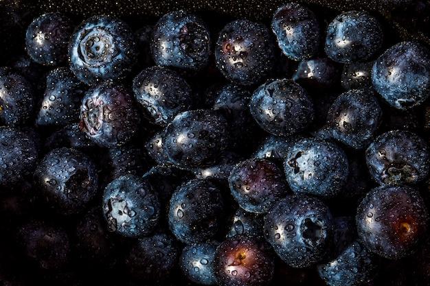 Свежая черника фон. текстура ягоды черники крупным планом с каплями
