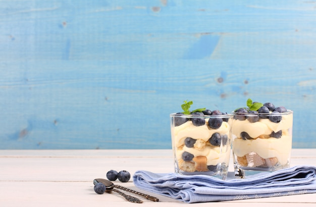 Fresh blueberry layered desert with mascarpone cream and cookies in glass