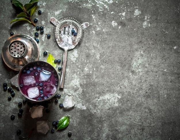 新鮮なブルーベリーを氷で振る。石のテーブルの上。